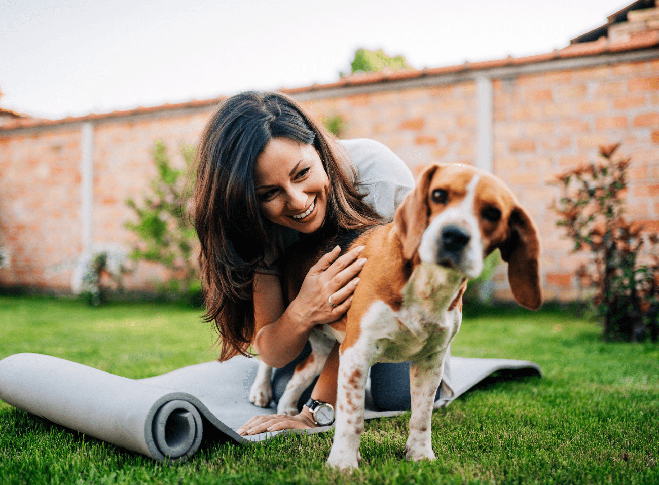 woman on a yoga mat in the yard playing with her dog