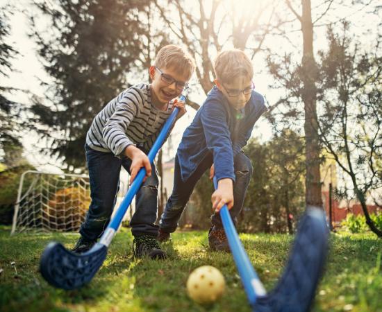 two boys playing hockey on their lawn